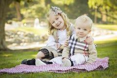 Lächelndes kleines Mädchen umarmt ihren Baby-Bruder am Park Stockbild