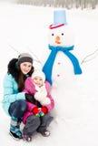 Lächelndes kleines Mädchen und junge Frau mit Schneemann am Wintertag Stockbild