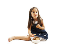 Lächelndes kleines Mädchen, welches das Plätzchen oder Keks, oben schauend isst Stockfotografie