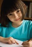 Lächelndes kleines Mädchen zeichnet. Stockfotografie