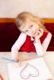 Lächelndes kleines Mädchen zeichnet Inneres. Valentinstag Stockfoto
