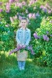 Lächelndes kleines nettes blondes Kindermädchen 4-9 Jahre mit einem Blumenstrauß der Flieder in den Händen in den Jeans und im He Stockfoto