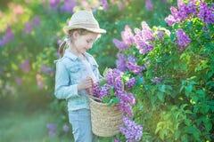 Lächelndes kleines nettes blondes Kindermädchen 4-9 Jahre mit einem Blumenstrauß der Flieder in den Händen in den Jeans und im He Lizenzfreies Stockbild
