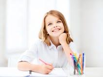Lächelndes kleines Studentenmädchen, das in der Schule zeichnet Stockbilder