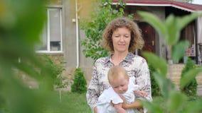 Lächelndes Kleinkind mit Mutter Lebenanfangkonzept Geschäftsdame mit einem Kind Baby auf Mutter ` s Händen stock footage