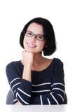 Lächelndes Kursteilnehmermädchen, das am Schreibtisch sitzt Lizenzfreie Stockfotos