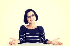 Lächelndes Kursteilnehmermädchen, das am Schreibtisch sitzt Stockbilder