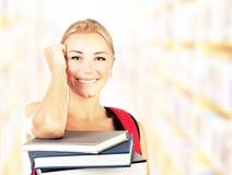 Lächelndes Kursteilnehmermädchenportrait mit Büchern lizenzfreie stockbilder
