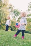 Lächelndes lachendes Händchenhalten des Mädchens und des Jungen und wellenartig bewegende amerikanische Flagge, Außenseite im Par Stockbild