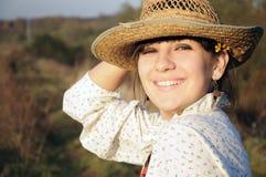 Lächelndes landwirtschaftliches Mädchen mit Strohhut Lizenzfreies Stockfoto