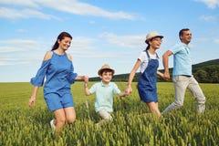 Lächelndes Laufen der glücklichen Familie auf dem Feld in der Natur Lizenzfreie Stockbilder