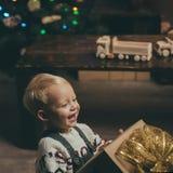 Lächelndes lustiges Kind in Sankt-Hut, der in der Hand Weihnachtsgeschenk hält Nettes Baby, frohe Weihnachten Fröhliches Weihnach lizenzfreies stockfoto