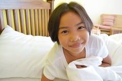 Lächelndes Mädchen auf dem Bett stockfoto