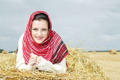 Lächelndes Mädchen auf einem Stapel Stroh Lizenzfreie Stockfotos