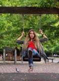 Lächelndes Mädchen auf Schwingen im Herbstpark Stockfotografie