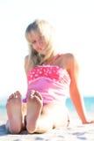Lächelndes Mädchen auf Strand, Fokus auf Füßen Lizenzfreie Stockfotografie
