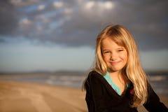 Lächelndes Mädchen auf Strand am Sonnenuntergang Stockfotografie