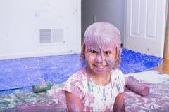 Lächelndes Mädchen bedeckt in den verschiedenen Farben der Farbe Stockfoto
