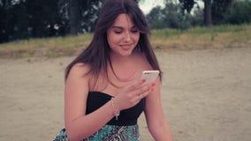Lächelndes Mädchen bei der Anwendung des Telefons auf dem Strand stock footage