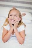 Lächelndes Mädchen, das auf Bett sich entspannt Lizenzfreie Stockfotografie