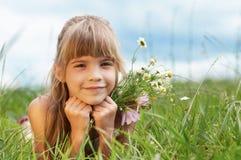 Lächelndes Mädchen, das auf Gras liegt Stockbild