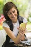 Lächelndes Mädchen, das auf ihrem Smartphone simst stockfotos