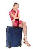 Lächelndes Mädchen, das auf Koffer sitzt Stockfotografie