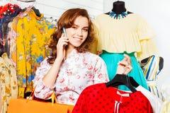 Lächelndes Mädchen, das auf Mobile und dem Einkauf spricht Stockfotos
