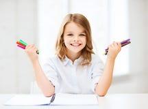 Lächelndes Mädchen, das bunte Filzstifte zeigt Lizenzfreies Stockbild