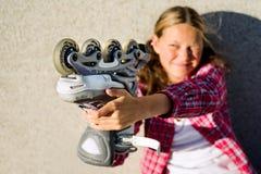 Lächelndes Mädchen, das in der Hand Rollschuhe hält Lizenzfreie Stockbilder