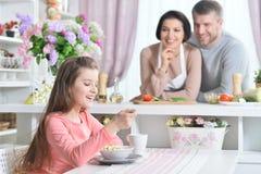 Lächelndes Mädchen, das an der Küche isst Stockfotografie