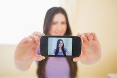 Lächelndes Mädchen, das ein Foto von mit ihrem Handy macht Stockfoto