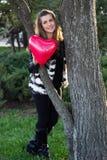 Lächelndes Mädchen, das ein Herz gemacht von den Ballonen hält Lizenzfreie Stockfotos