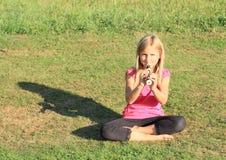 Lächelndes Mädchen, das eine Flöte spielt Stockfotos