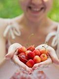 Lächelndes Mädchen, das eine Handvoll Kirschen anhält Stockfoto