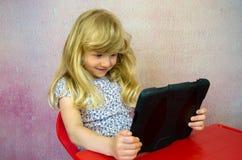 Lächelndes Mädchen, das eine Tablette hält Stockbild