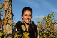 Lächelndes Mädchen, das in einem Weinberg steht stockfoto