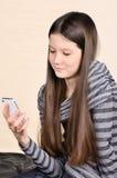 Lächelndes Mädchen, das einen Handy verwendet Lizenzfreie Stockbilder