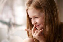 Lächelndes Mädchen, das Fenster betrachtet lizenzfreie stockfotos