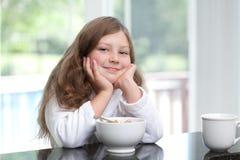 Lächelndes Mädchen, das Frühstückskost aus Getreide isst Stockfotos
