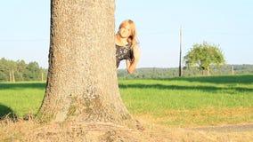 Lächelndes Mädchen, das hinter Baum wellenartig bewegt stock footage