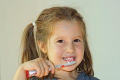 Lächelndes Mädchen, das ihre weißen Zähne wäscht Stockbild