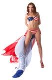 Lächelndes Mädchen, das im Badeanzug mit amerikanischer Flagge aufwirft Stockbild
