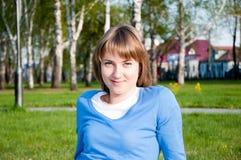 Lächelndes Mädchen, das im Park sitzt Stockbild