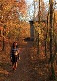Lächelndes Mädchen, das im Wald steht Stockbild