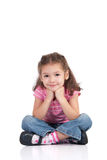 Lächelndes Mädchen, das mit den gekreuzten Fahrwerkbeinen sitzt stockfoto