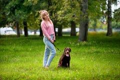 Lächelndes Mädchen, das mit Hund sich entspannt Lizenzfreies Stockfoto