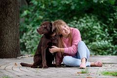Lächelndes Mädchen, das mit Hund sich entspannt Labrador, das als Nächstes sitzt Lizenzfreie Stockbilder