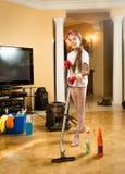 Lächelndes Mädchen, das mit Staubsauger beim Handeln des Säuberns aufwirft Stockfoto