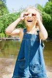 Lächelndes Mädchen, das picknick auf dem Flussufer hat Stockfoto